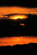 Sunrays try to burst through the clouds at sunrise near Homer, Alaska.