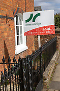 Estate agent property sold sign outside red brick historic house, Marlborough, Wiltshire, England, UK