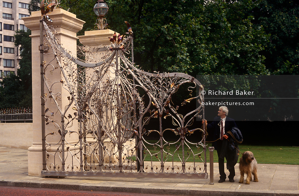 A passer-by admires workmanship of the Queen Mother's Memorial Gates at the western entrance to Hyde Park in central London. The Queen Mother Gates - officially known as the 'Queen Elizabeth Gate' - lead into The Carriage Road in Hyde Park from Park Lane and are located to the rear of Apsley House at Hyde Park Corner. The Queen Mother Gates where opened by Her Majesty Queen Elizabeth II on 6 July 1993. They where built by money raised by a number of benefactors and public donors under the patronage of HRH Prince Michael of Kent to honour Her Majesty Queen Elizabeth The Queen Mother. The six gates, railings and lamps are made from forged stainless steel and bronze to designs by the noted metal artist / sculptor Giusseppe Lund.
