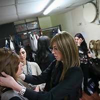 Miri Beillin, an ultra orthodox Jewish woman, fixes the wig on the model's head during her work as a stylist at fashion show for ultra orthodox women.