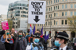 A man holds a placard reading Don't Talk To Them behind Metropolitan Police Liaison Team (PLT) officers during a Kill The Bill demonstration in Trafalgar Square as part of a National Day of Action to mark International Workers Day on 1st May 2021 in London, United Kingdom. Nationwide protests have been organised against the Police, Crime, Sentencing and Courts Bill 2021, which would grant the police a range of new discretionary powers to shut down protests.