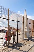 Mexican Family Looking Through Tijuana Boundary Fence, Border Field State Park, California, USA