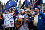 Anti Brexit pro Europe demonstrator sings a pro European song while Vote Leave protesters barrack her as remainers wave European Union and Union Jack flags in support in Westminster on the day of the 'meaningful vote' when MPs will back or reject the Prime Minister's Brexit Withdrawal Agreement on 15th January 2019 in London, England, United Kingdom.
