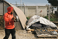 A man living in the Moria refugee camp makes tea as he walks past a semi collapsed tent, where some asylum seekers are living. Lesvos island, Greece.