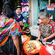 A woman sells various snacks and grains at the main market in Antigua, Guatemala.