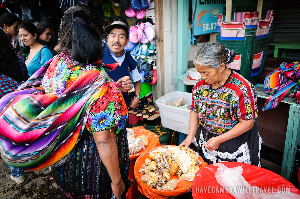 A woman sells various snacks and grains at the main market in Antigua, Guatemala.