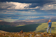 A visitor enjoys the view from along the Top of the World Highway, Yukon Territory, Canada.