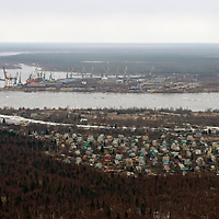Cranes for loading ships crowd a riverbank in the northern Russian port of Arkhangel'sk, near the Dvinskay Gulf of the White Sea, leading to the Arctic Ocean.