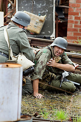Re-enactor dressed as a Panzer Grenadier from the Elite German Heer GrossDeutschland Division recieves medical attention from a field medic during a battle re-enactment at the Elsecar Heritage Centre 1940s Wartime Weekend 4 September 2010 .Images © Paul David Drabble..