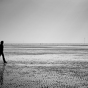 Silhouettes crossing beach at low tide, Liverpool, England (October 2006)
