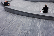 A lonely-looking man spends his lunchtime in an empty urban landscape near a kissing couple in London.