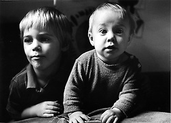 Young boy looking thoughtful sitting next to toddler looking surprised,