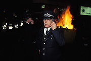 As the flames of a fire strted deliberately burns in the background, police officer listens to his radio during disturbances about the Poll Tax, the controversial property tax imposed by Margaret Thatchers government and which ultimately brought about her downfall weeks later, on 20th October 1990, in London, England.