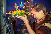 28 NOVEMBER 2012 - BANGKOK, THAILAND: A woman prays before launching her krathong on Loy Krathong at Wat Yannawa in Bangkok. Loy Krathong takes place on the evening of the full moon of the 12th month in the traditional Thai lunar calendar. In the western calendar this usually falls in November. Loy means 'to float', while krathong refers to the usually lotus-shaped container which floats on the water. Traditional krathongs are made of the layers of the trunk of a banana tree or a spider lily plant. Now, many people use krathongs of baked bread which disintegrate in the water and feed the fish. A krathong is decorated with elaborately folded banana leaves, incense sticks, and a candle. A small coin is sometimes included as an offering to the river spirits. On the night of the full moon, Thais launch their krathong on a river, canal or a pond, making a wish as they do so.    PHOTO BY JACK KURTZ