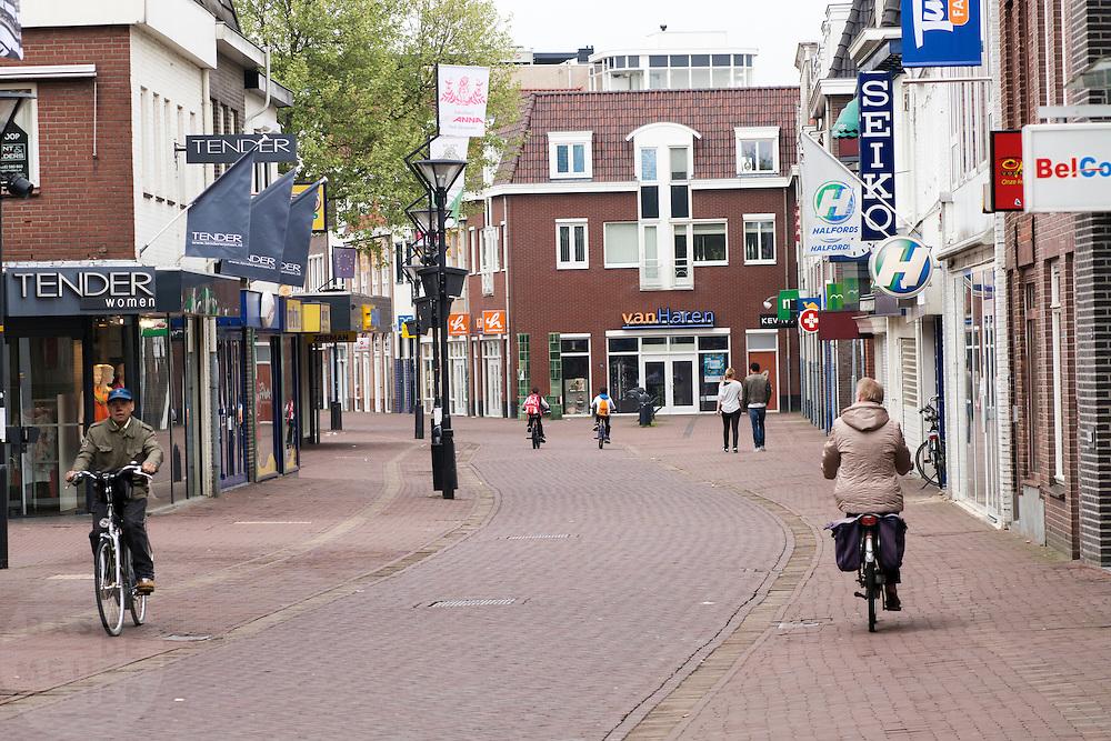 Fietsers rijden door het centrum van Zevenaar, een plaats in de streek De Liemers in het oosten van Nederland. <br /> <br /> Cyclists ride through the center of Zevenaar, a place in the region the Liemers in the east of the Netherlands.