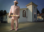 Bishop Dready Manning stands proudly with his guitar in front of his church in Roanoke Rapids North Carolina.