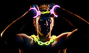 Portrait of a handcuffed man with glowing chain and handcuffs.Black light