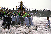 A mikoshi and supporters in the surf at sunrise during the Hamaorisai matsuri on Southern Beach in Chigasaki, Kanagawa, Japan. Monday July 18th 2005. The festivals marks the celebration of Marine Day in July. Over thirty Mikoshi or portable shrines are carried through the night from surrounding shrines to arrive on the beach for sunrise. They are then carried into the surf to purify them.