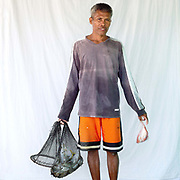 Salvador Layaog (48), fisherman with his catch, Pooc, Bantayan Island, The Philippines. Every morning at 7 am fisherwomen meet fishermen as they return from the sea with their catch. Women sort the fish by size and type, then weigh and distribute the fish between saleswomen to be sold on to local customers. On November 6 2013 Typhoon Haiyan hit the Philippines and was one of the most powerful storms to ever make landfall.  Three-quarters of the island's population of about 136,000 depend on fishing as their main source of income. Thousands lost their boats and equipment in the storm. Oxfam is working to support the immediate and long-term needs of affected communities on Bantayan Island.