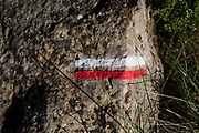 Detail of red and white stripes painted on a rock showing cross-country walkers the route on French national trekking network, the GR36, on 21st May 2017, in Lagrasse, Languedoc-Rousillon, south of France. Lagrasse is listed as one of Frances most beautiful villages and lies on the famous Route 20 wine route in the Basses-Corbieres region dating to the 13th century.