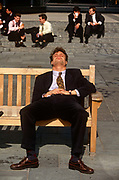 Snatching a well-earned lunchtime snooze, a young office worker in Broadgate in the City of London. The young man sits with legs wide apart, oblivious to his posture.<br /> The bench which is owned by the Corporation of London, provided in this public space for those emerging from their offices to enjoy mid-day sunshine, a chance to steal a few precious minutes sleep before re-entering their office buildings and returning to desks.