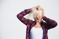 Young woman playing with her hairs and dancing in front of wall, Bavaria, Germany