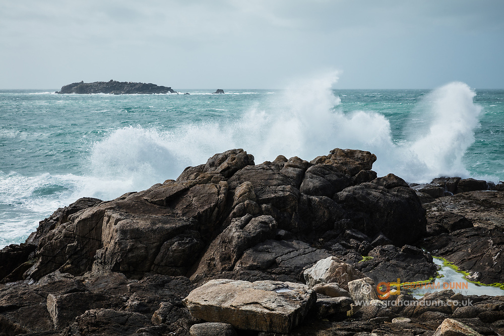 Waves travel unhindered across the Atlantic Ocean and arrive at Hell Bay, Bryher, with full force. High winds and a Spring Tide led to a dramatic display as they crashed into the rocks. Scilly Rock can be seen in the distance. Isles of Scilly, UK.