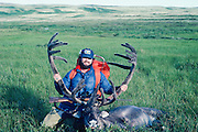 Man proudly showing off his caribou prize after a hunt.