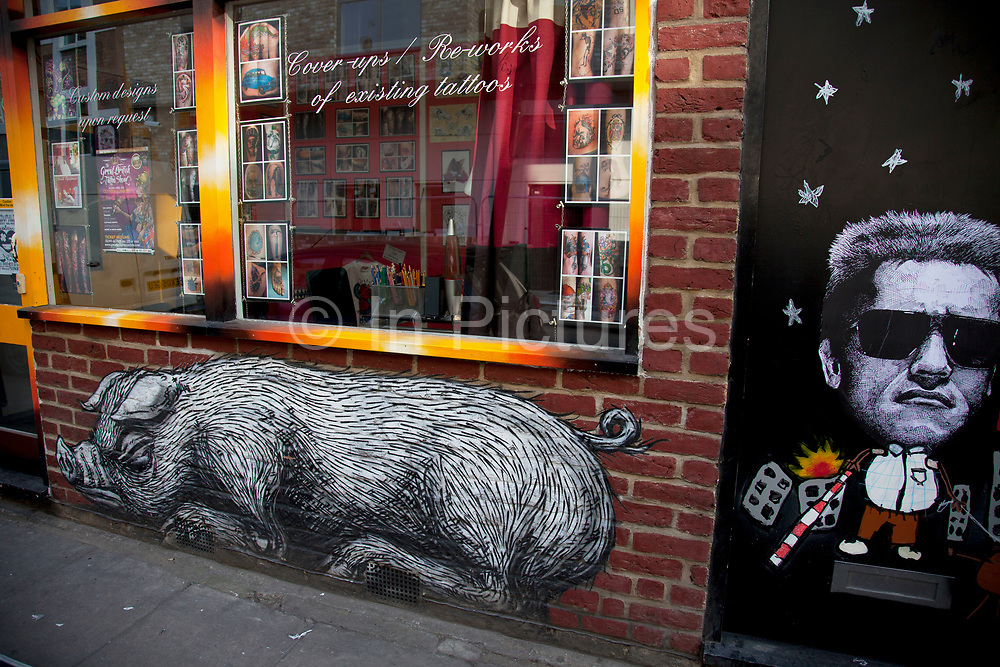 Roa is a Belgian street artist renowned for his giant black and white animals which can be found on walls and shutters in varying states of decay. Seen here is his pig in a shop doorway on Bacon Street just off Brick Lane. There are also a few Rats and Birds which reside on shop shutters along Brick Lane.<br /> <br /> Street art in the East End of London is an ever changing visual enigma, as the artworks constantly change, as councils clean some walls or new works go up in place of others. While some consider this vandalism or graffiti, these artworks are very popular among local people and visitors alike, as a sense of poignancy remains in the work, many of which have subtle messages.