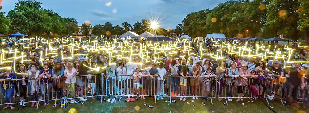 © Licensed to London News Pictures. 27/06/2015. Witney, Oxfordshire. The crowd draw the letter L in silent tribute to LIBERTY BAKER. 3000 attended the very first Lib Fest that took place in memory of Witney schoolgirl Liberty Baker who was killed on the way to school by 18 year old driver Robert Blackwell. PAUL BAKER, the father of Liberty was accused by Police of harassing the Blackwell family and was due in front of magistrates, but it was dropped at the last minute. Photo credit : MARK HEMSWORTH/LNP