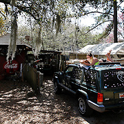 """Allison Kopanski, 18, of Beaufort, reads from a book while basking in the sun on top of her Jeep at her home in the Pigeon Point neighborhood in Beaufort on March 17, 2015.  """"Sun was out but it was too far to get to the beach,"""" said Kopanski."""