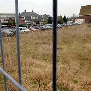 NLD/Huizen/20060104 - Braakliggend terrein Keucheniusstraat Huizen met geparkeerde auto's ervoor, hek, auto, parkeren, open,