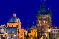 View of tower of  the Charles Bridge and Prague skyline at night.