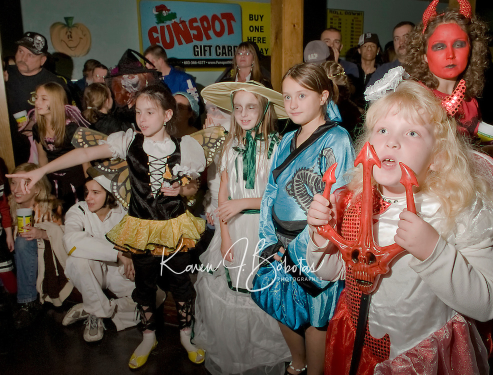 Butterfly Dakota Goduen, Vampire Rebecca Simison, Geisha Jade Hildebrand and Double Trouble Teka Marie Phillips admire the hundreds of costumes parading through Funspot on Saturday evening for their annual Halloween Party and Costume Judging.  (Karen Bobotas/for the Laconia Daily Sun)
