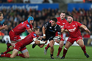Kieron Fonotia of the Ospreys ©, despite being surrounded by Scarlets players gets his pass away to teammate Jeff Hassler (not in pic) .  Guinness Pro14 rugby match, Ospreys v Scarlets at the Liberty Stadium in Swansea, South Wales on Saturday October 7th 2017. <br /> pic by Andrew Orchard, Andrew Orchard sports photography.
