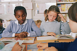 Junior school girls sitting at desks in classroom reading books,