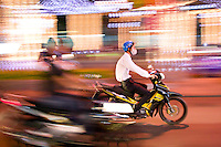 Motorbikes and scootes whizz around the streets of Saigon at night.