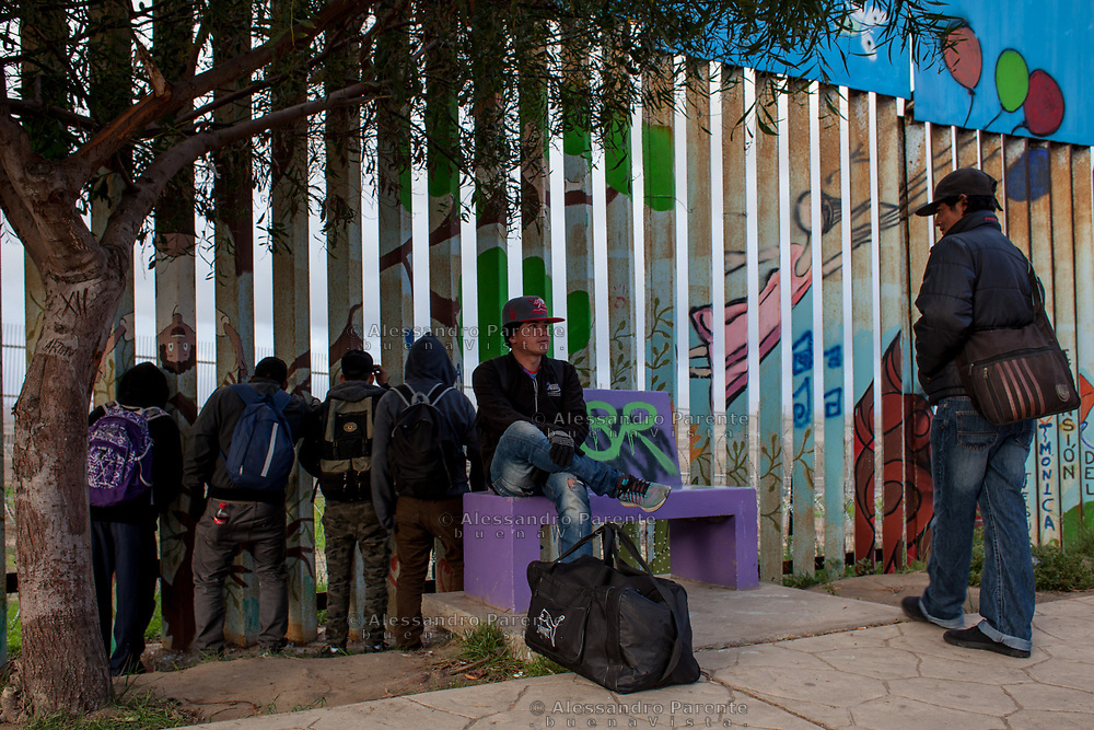 Migrants group watching through the fence