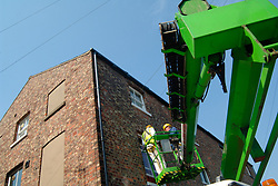Painting and decorating contractors paint the outside of a house using a hydraulic crane instead of a ladder which is dangerous UK