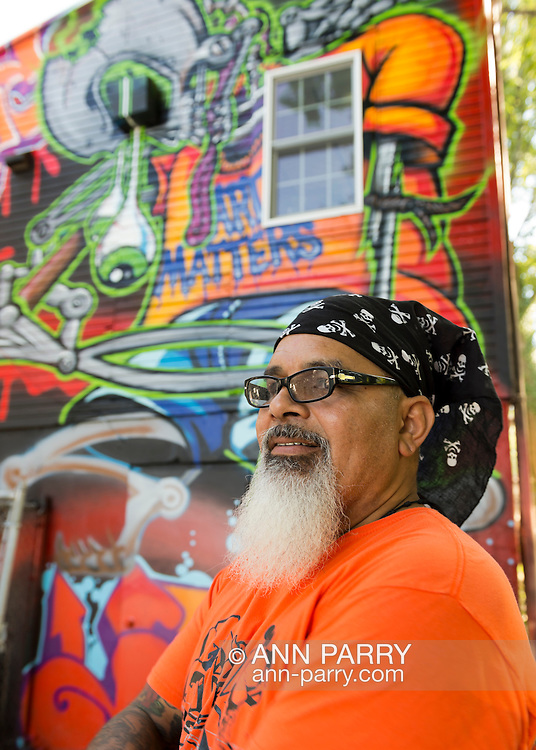"""Huntington, New York, U.S. 24th August 2013. INK76, street artist ALEXANDER SILVA from Brooklyn, is holding a spray paint can he used to help paint  the """"Art Matters"""" wall, with legendary street artist SONIC BAD, on the back of the Huntington Arts Council building, during the the art event """"Off the Walls"""" Block Party, by SPARKBOOM, a project the council created to help emerging artists, showcase talents, and help its artistic family network."""
