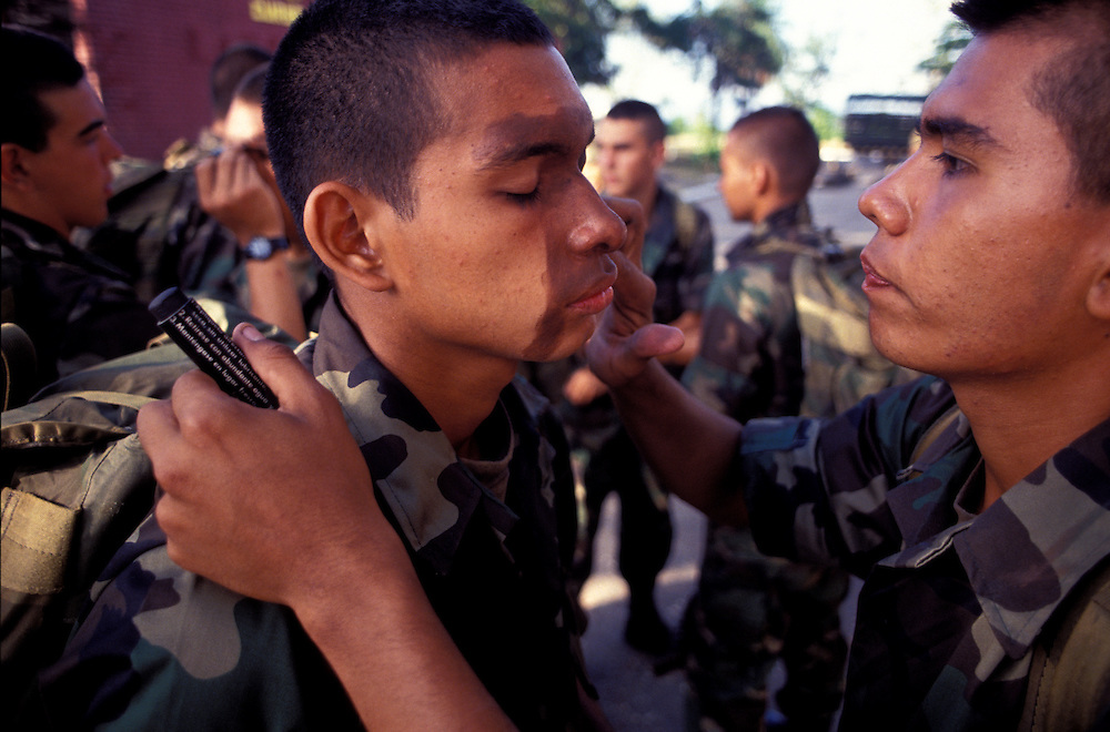 Recruits apply each other with camoflague cream during Commando training, Tolemaida.