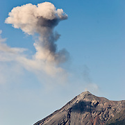Volcán de Fuego emits a large puff of ash and smoke near Antigua Guatemala. Famous for its well-preserved Spanish baroque architecture as well as a number of ruins from earthquakes, Antigua Guatemala is a UNESCO World Heritage Site and former capital of Guatemala.