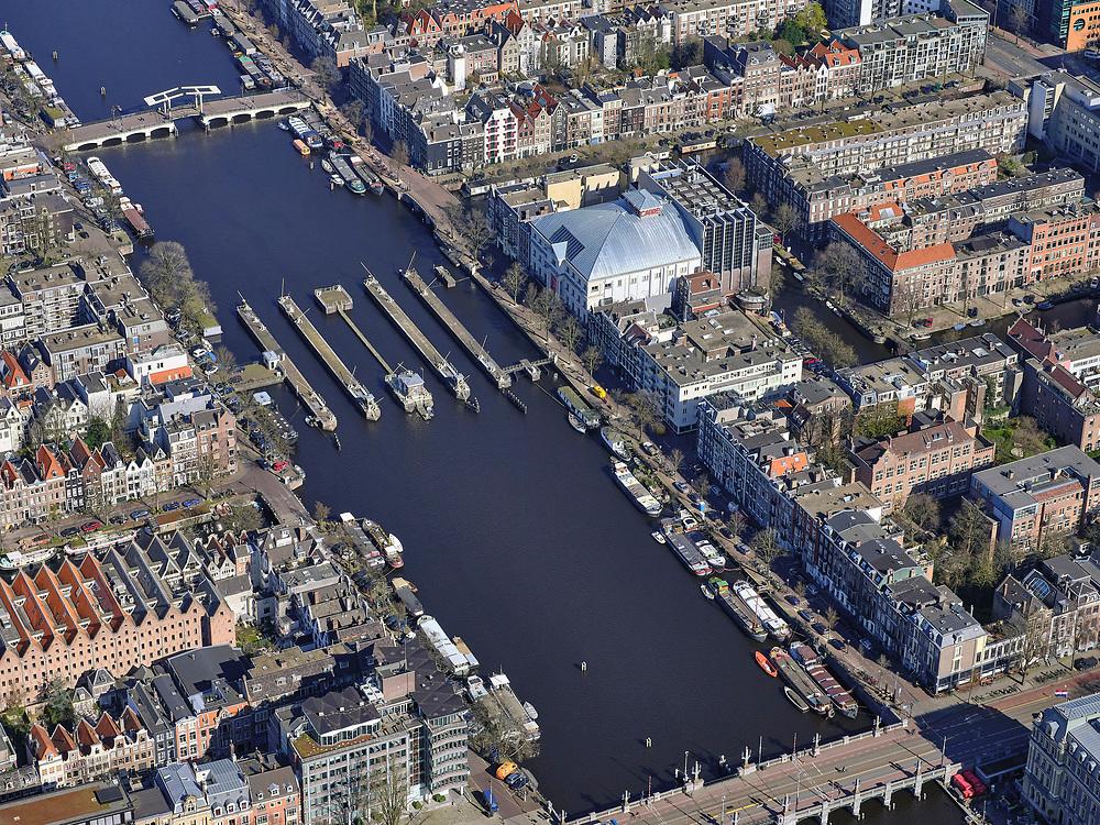 Nederland, Noord-Holland, Amsterdam; 23-03-2020; Amstel en Amstelsluizen met Koninklijk Theater Carré<br /> Het publieke leven in het centrum van de hoofdstad is bijna geheel stil komen te liggen als gevolg van het Corona virus. Niet alleen is alle horeca dicht, ook veel winkels en andere bedrijven zijn gesloten. Het publiek blijft over het algemeen binnen, de straten en pleinen zijn stil.<br /> River Amstel, city centre.<br /> Public life in the center of the capital has come to a complete standstill as a result of the Corona virus. Not only are all pubs, coffee shops and restaurants,  closed, many shops and other companies are also closed. The public generally stays inside, the streets and squares are very quiet.<br /> <br /> luchtfoto (toeslag op standaard tarieven);<br /> aerial photo (additional fee required)<br /> copyright © 2020 foto/photo Siebe Swart