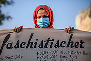 A protester holds a banner with the names of past victims of racist terror in Germany, as people take part in a memorial demonstration to the victims of the Hanau terror attack, in Berlin, Germany, August 19, 2020. Thousands of protesters marched through the German capital's Neuköln district in remembrance of the Hanau shootings, in which ten people were killed and five others wounded. The shooting spree was committed on February 19, 2020 by a far-right extremist targeting two shisha bars and kiosks at the Hessian city of Hanau near Frankfurt. The gunman was identified as 43-year-old Tobias Rathjen. The majority of the victims were Germans with migrant backgrounds, among the victims was also the perpetrator's mother. (Photo by Omer Messinger)