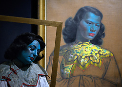 "© Licensed to London News Pictures. 18/03/2013. London, UK Caberet singer Tricity Vogue, whose successful Edinburgh Fringe Theatre Festival performances were inspired by 'Chinese Girl' poses with the original painting. Press call before the auction of ""Chinese Girl"" by Vladimir Tretchikoff at Bonhams in London today 18th March 2013. The painting is said to be the most widely reproduced and recognisable painting in the world because of its wide reproduction in 1950's art prints. It is expected to fetch 300,000-500,000 GBP at auction on the 20th March. Photo credit : Stephen Simpson/LNP"