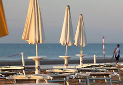 THEMENBILD - geschlossene Sonnenschirme, leere Liegestühle und Spaziergänger an einem Sandstrand, aufgenommen am 16. Juni 2018, Lignano Sabbiadoro, Österreich // closed umbrellas, empty beach chairs and strollers on a sandy beach on 2018/06/16, Lignano Sabbiadoro, Austria. EXPA Pictures © 2018, PhotoCredit: EXPA/ Stefanie Oberhauser
