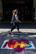 A woman walks past a message of love for the National Health Service (NHS), painted on the ground outside Selfridges department store on a near-deserted Oxford Street in London on Thursday, May 28, 2020. The government in Britain eased restrictions across England as a slow loosening of the coronavirus lockdown gets underway, with people now encouraged to return to work if unable to do so from home and unlimited outdoor exercise now allowed. As the row over Prime Minister Boris Johnson's top aide Dominic Cummings' Durham trip, continues, the prime minister's populist appeal has been hammered by the news that, as the coronavirus outbreak raged, chief adviser Cummings drove 250 miles (400 kilometres) to his parents' house while he was falling ill with suspected COVID-19 allegedly flouting lockdown rules that the government had imposed on the rest of the country. (Photo/ Vudi Xhymshiti)