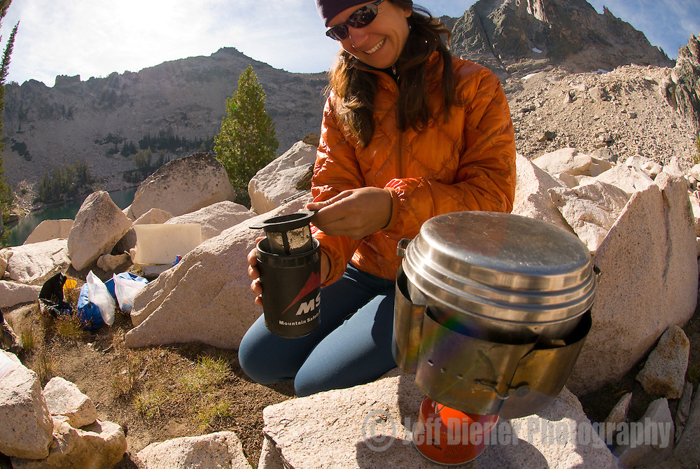 A young woman makes backcountry coffee while camping in the Sawtooth Mountains, Idaho.