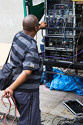 London, August 30th 2015. Its complicated: A man wires up his amplification system at one of the many sound systems dotted around the route of the procession as revellers await the start of the Notting Hill Carnival.