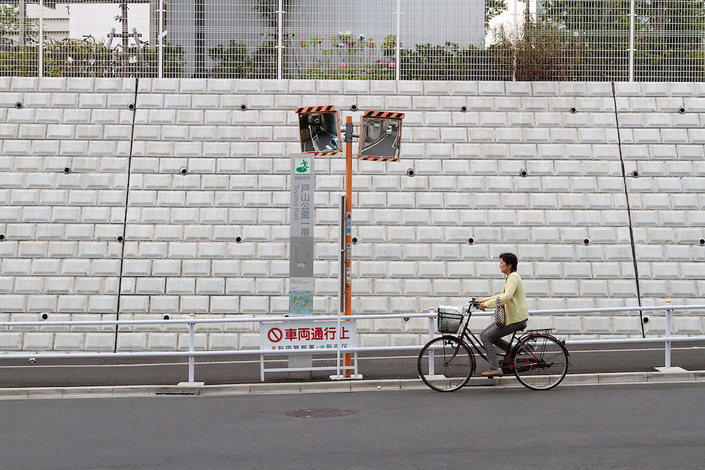 Woman rides a bicycle by some mirrors used for road safety in Okubo,  Shinjuku, Tokyo, Japan. Friday June 17th 2016